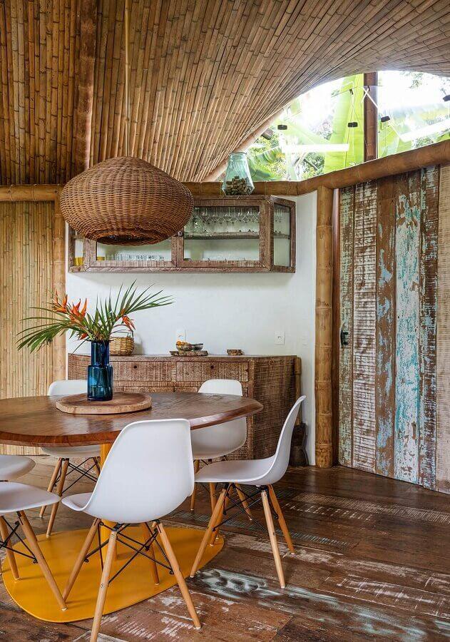 sala de jantar simples decorada com luminária rústica redonda e cadeiras brancas Foto Histórias de Casa