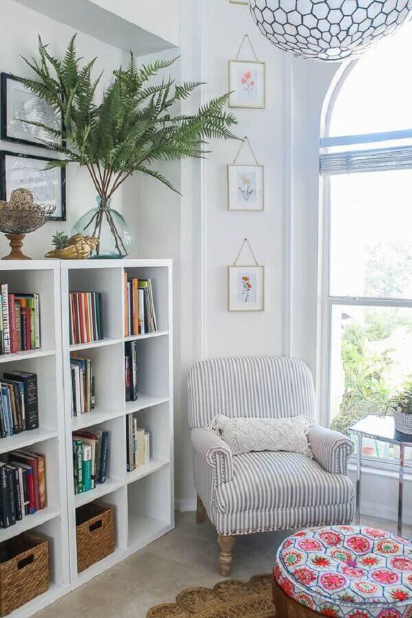 sala decorada com estante branca para livros e poltrona para leitura listrada Foto House Mix
