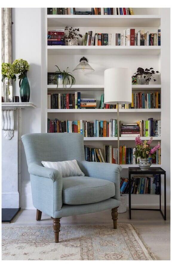 sala decorada com estante de livros branca e poltrona para leitura clássica Foto Pinterest