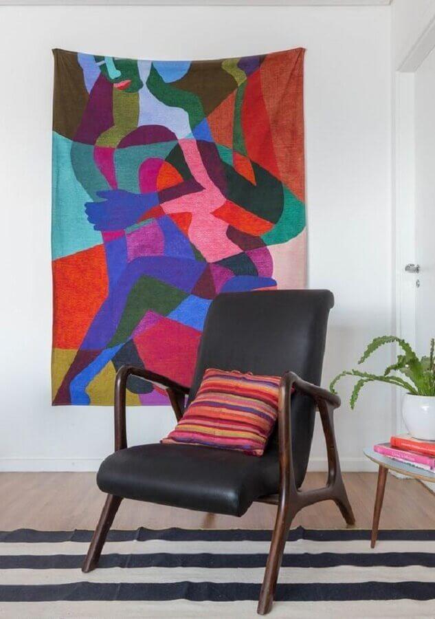 sala decorada com poltrona de couro preta e tecido na parede colorido Foto Histórias de Casa