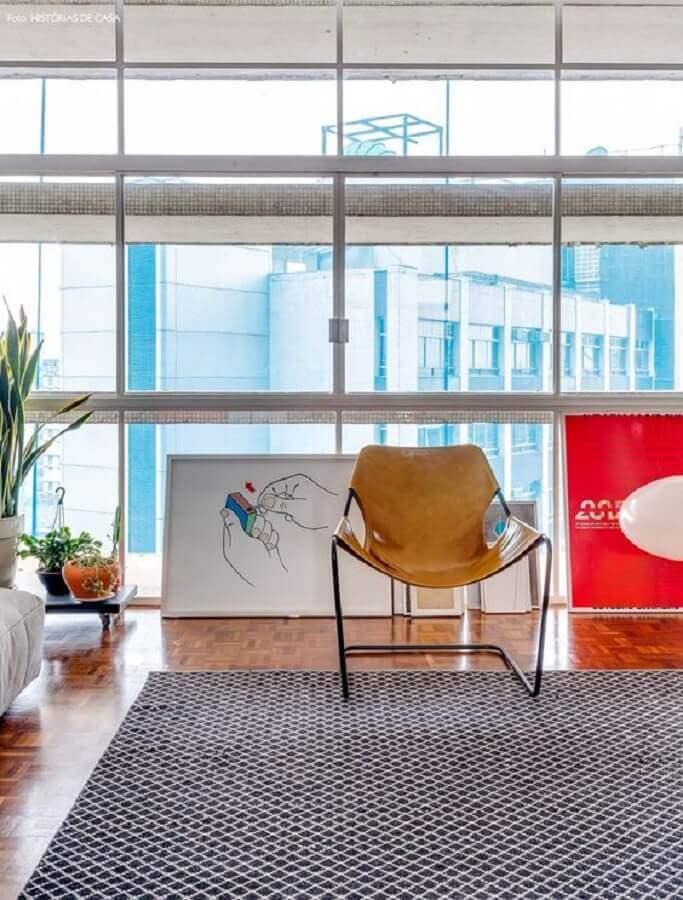 sala decorada com tapete geométrico e poltrona de couro moderna Foto Histórias de Casa