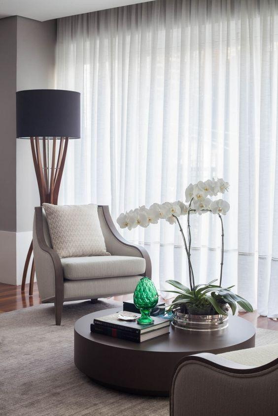 Sala de estar com vaso de orquídea no centro