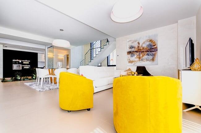 As costas do sofá branco delimita a área da sala de estar nos espaços integrados