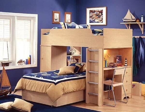 A beliche com escrivaninha de madeira traz neutralidade para o dormitório azul