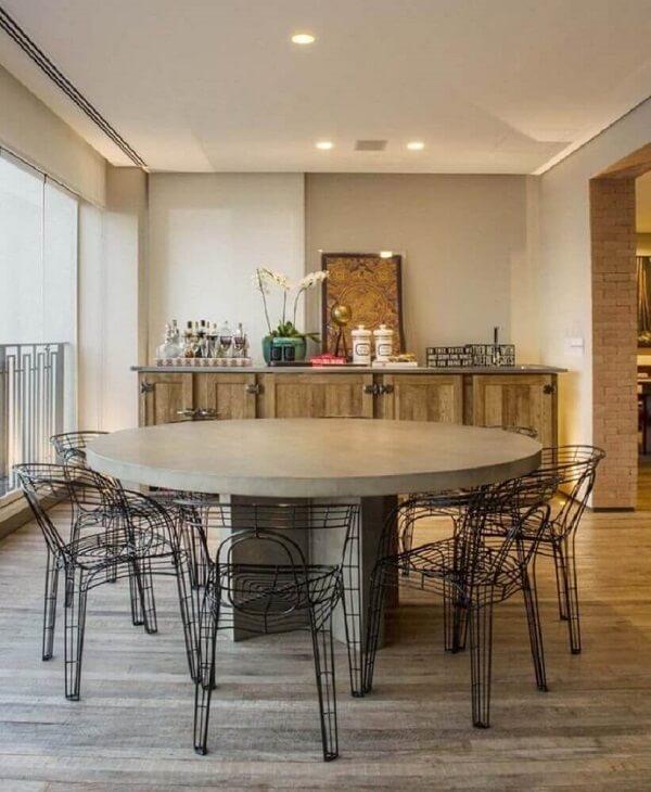 A cadeira cromada preta decora a varanda com buffet de madeira
