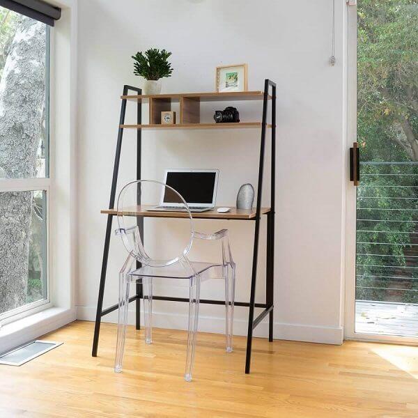 A cadeira de acrílico transparentes se conecta com a estrutura da escrivaninha de ferro e madeira