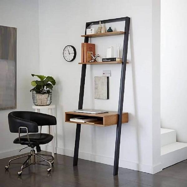 A cadeira preta giratória serve de acesso para a escrivaninha de ferro e madeira