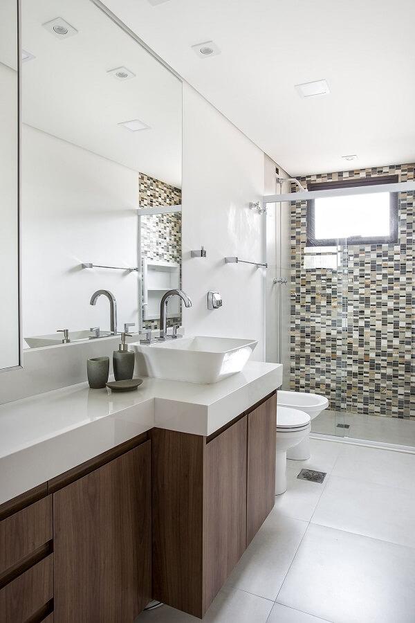 A cuba pia de apoio para banheiro foi posicionada sobre um gabinete amadeirado