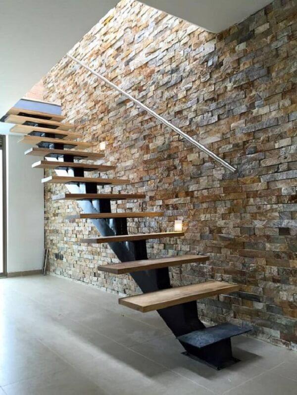 A escada com revestimento de parede interna com pedra canjiquinha fica ainda mais moderna