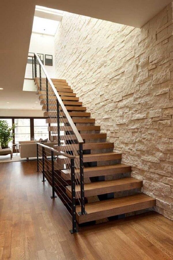 A escada de madeira ganha um revestimento de parede com pedra canjiquinha