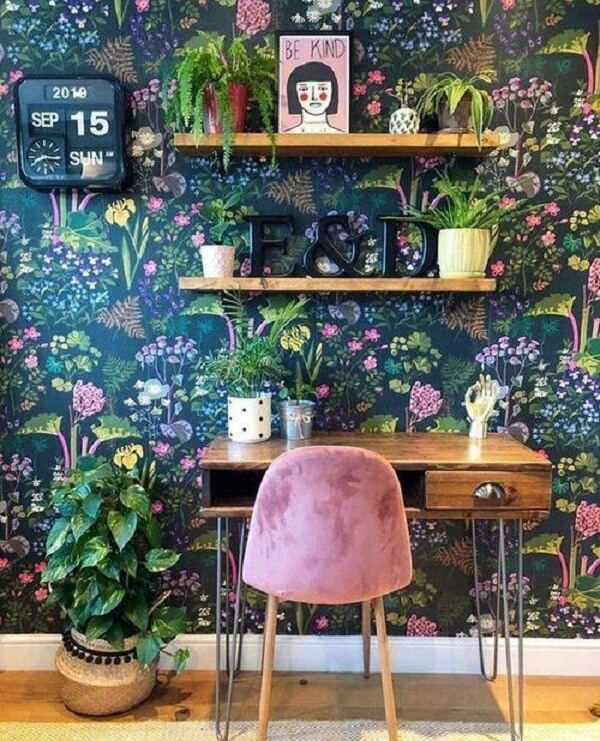 A escrivaninha antiga de madeira traz neutralidade para o ambiente com papel de parede floral