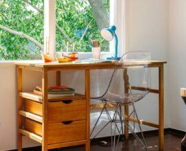 A escrivaninha de madeira maciça posicionada próxima a janela recebe muita luz natural