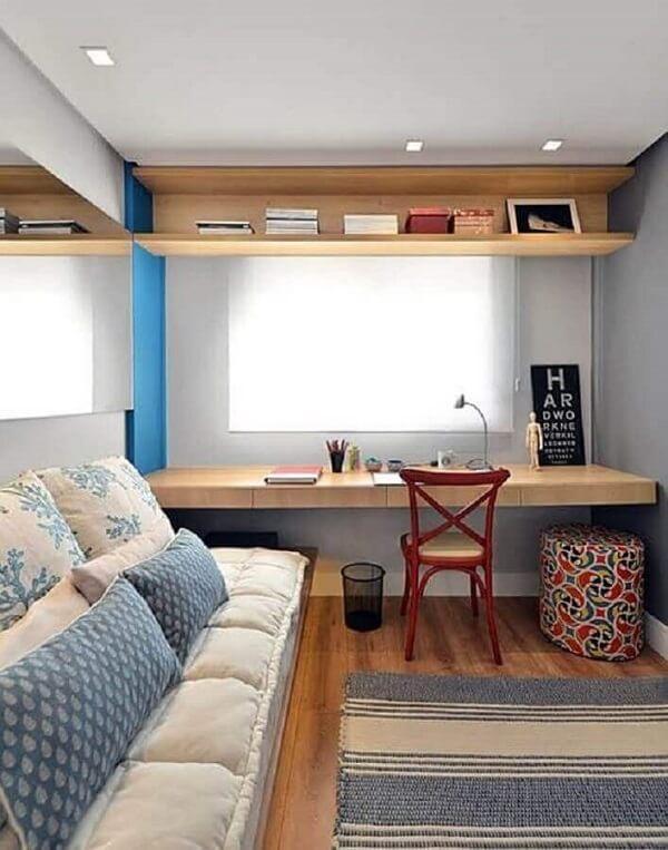A escrivaninha de madeira para quarto foi fixada próxima a janela para receber mais luz natural