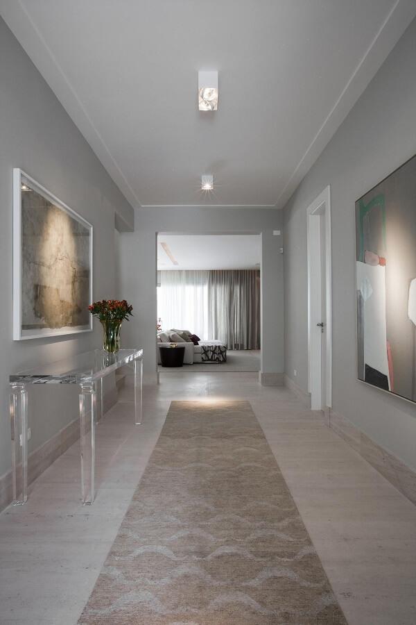 A luminária para corredor interno branca se conecta com o aparador acrílico e o tapete com estampa neutra