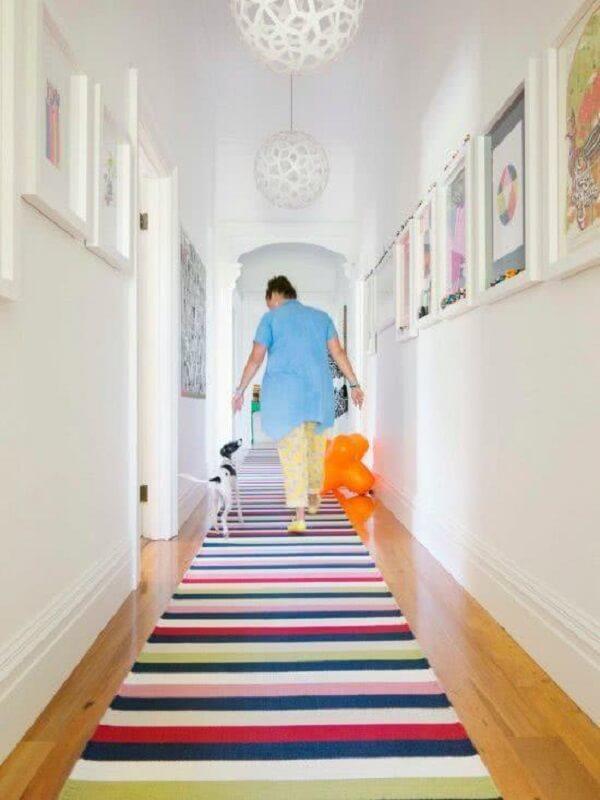 A luminária para corredor interno branca se harmoniza com o tapete colorido