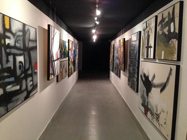 A luminária para corredor interno do tipo trilho destaca obras de arte no ambiente