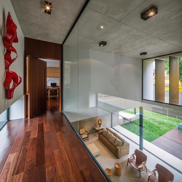 A luminária para corredor interno em tom preto se conecta com a decoração do espaço
