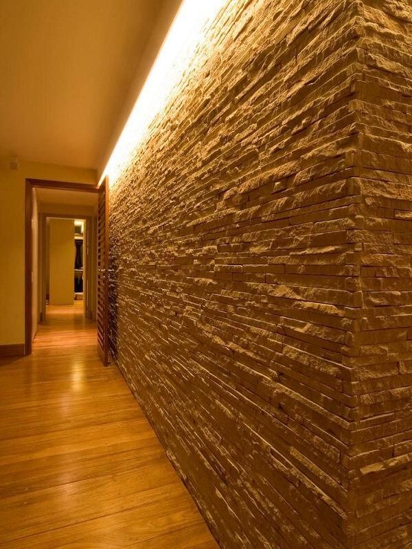 A luminária para corredor pequeno ilumina a área de passagem e realça a parede revestida com pedra canjiquinha
