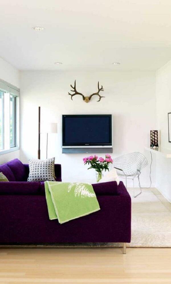 A manta para sofá roxo na cor verde traz um contraste interessante