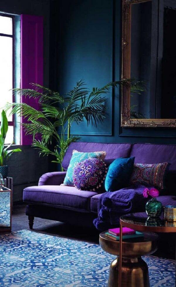 A parede azul combinou perfeitamente com o sofá roxo da sala