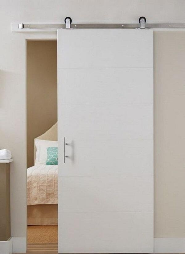 A porta de correr branca para quarto é discreta e decora com elegância o espaço