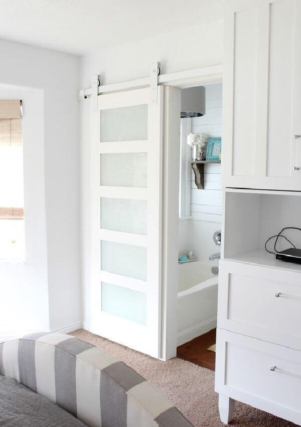 A porta de correr branca para quarto é discreta e se encaixa perfeitamente nesse dormitório pequeno