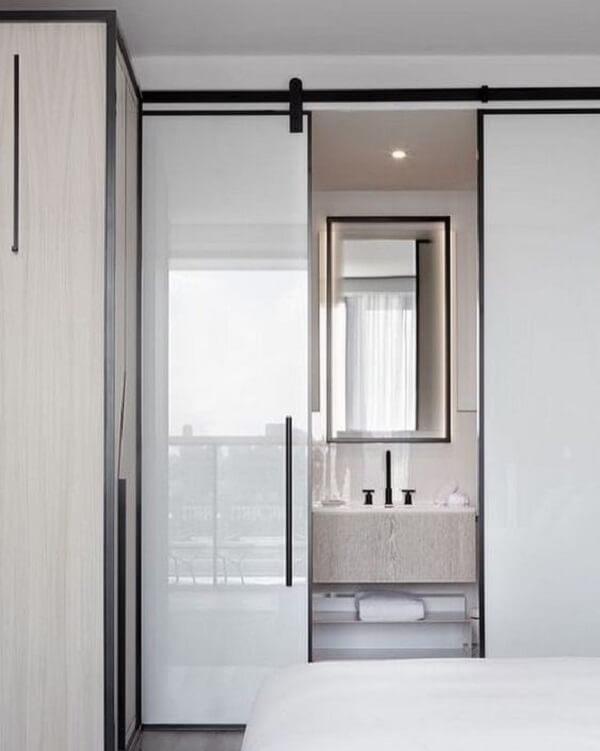 A porta de correr para quarto quando fechada esconde o banheiro com cuba esculpida