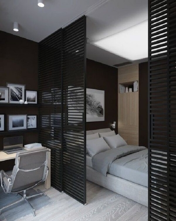 A porta para quarto de correr preta com estrutura vazada separa a cama da escrivaninha