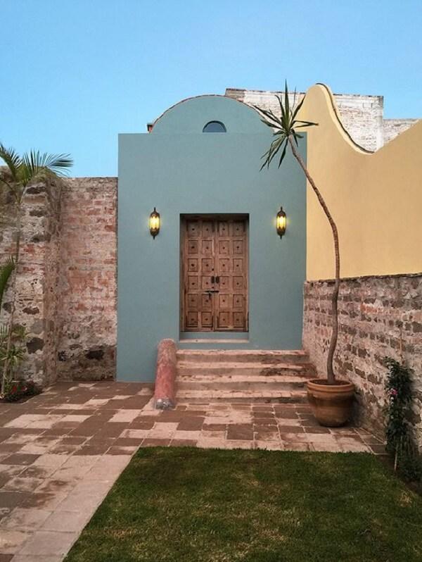 Arandela colonial preta se destaca na parede externa do imóvel
