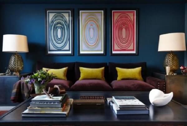 As almofadas amarelas sobra o sofá roxo trazem luz para a decoração