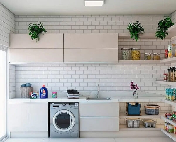 Bancada ampla e revestimento para lavanderia branco decoram o espaço