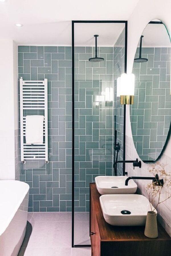 Bancada de madeira escura, cuba de apoio para banheiro branca e elementos em preto reforçam o estilo industrial