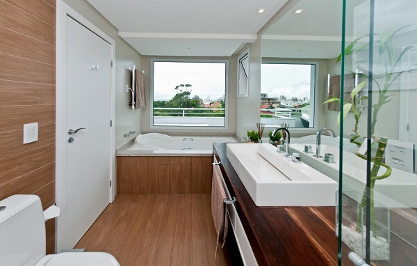 Bancada de madeira extensa acomoda uma linda e cuba de apoio para banheiro branca