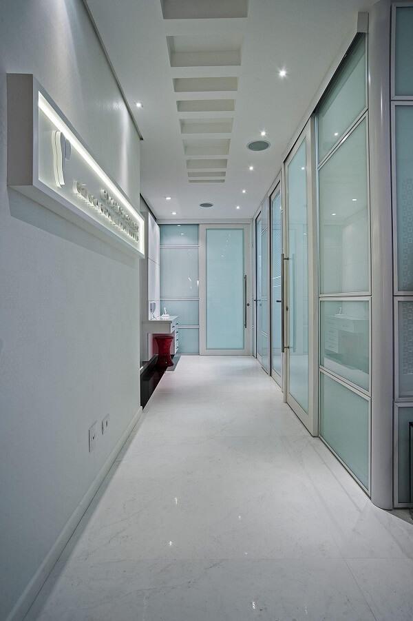 Corredor com portas de vidro e pontos e luminária para corredor embutida no teto discreta