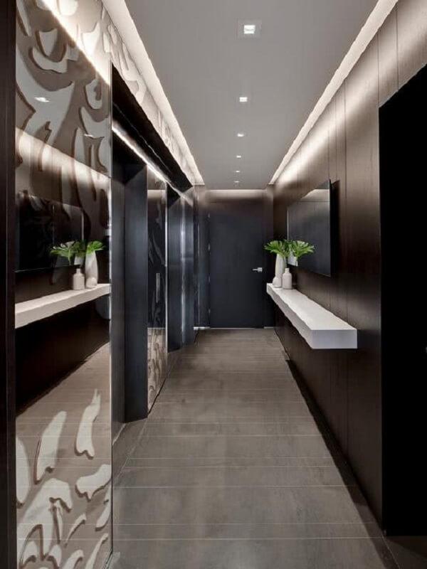 Corredor moderno com parede revestida em madeira e luminária de teto de embutir