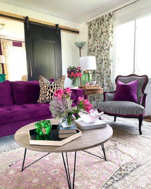 Decoração com sofá roxo e almofadas estampadas