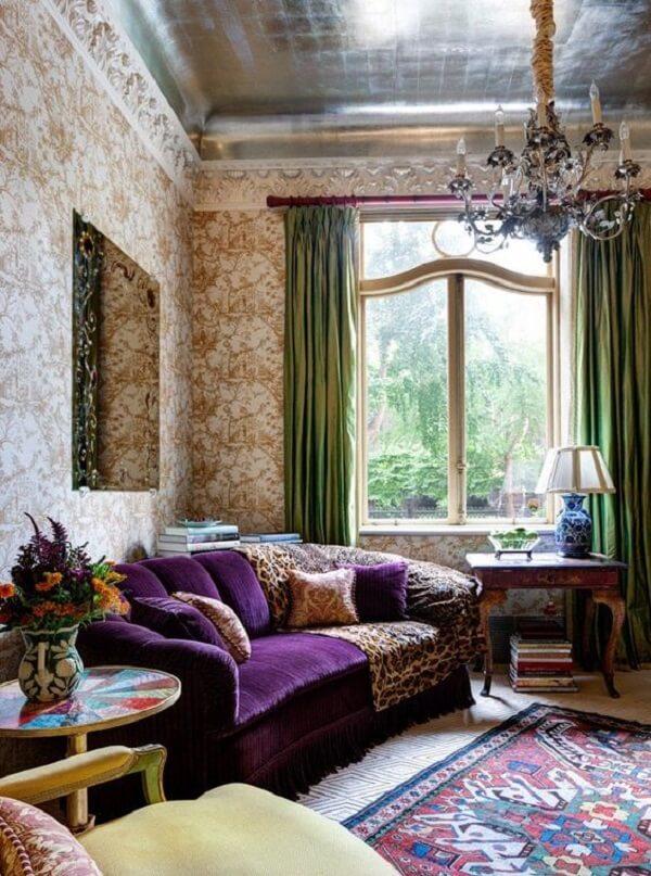 Decoração com sofá roxo e tapete estampado