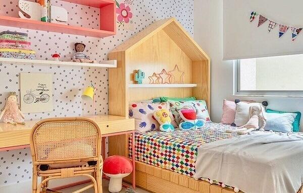 Decoração divertida com escrivaninha de madeira e cama com cabeceira de casinha