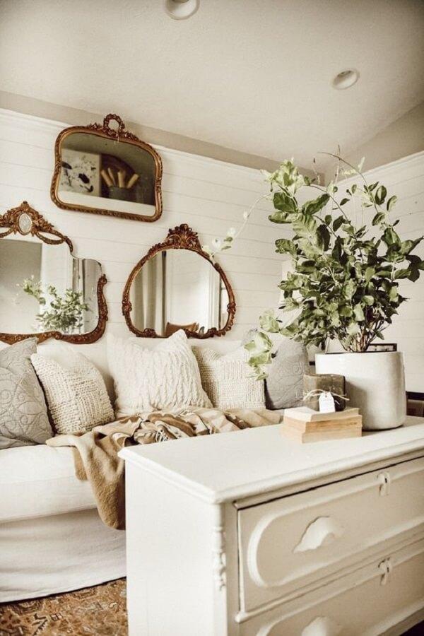 Diferentes modelos de espelho vintage foram posicionados sobre o sofá da sala