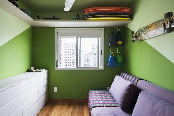 Dormitório criativo com paredes em tom verde e sofá cama roxo