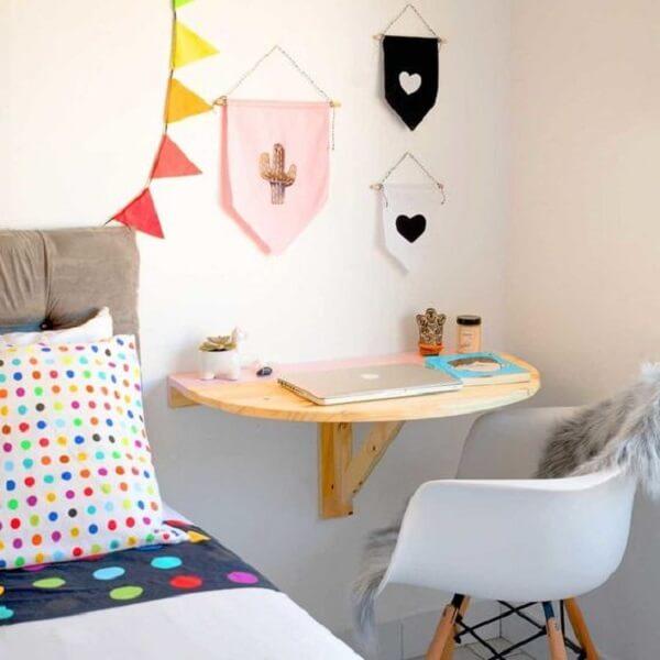Escrivaninha de madeira rústica suspensa em formato meia lua otimiza o espaço do quarto