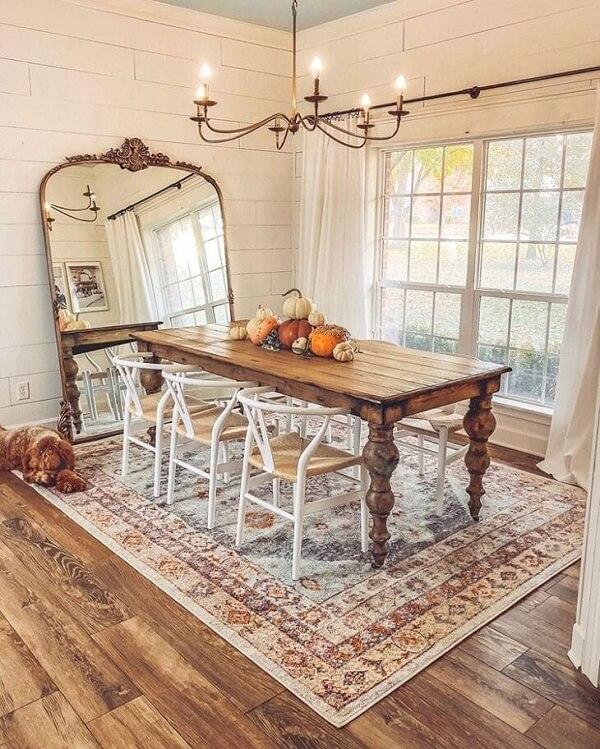 Espelho vintage de chão combinado com o acabamento do lustre realçam a beleza da sala de jantar