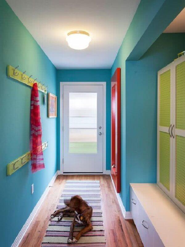 Modelo de luminária para corredor interno com parede azul e decoração vermelha e verde