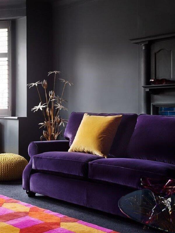 Modelo de sofá roxo escuro em veludo e almofada amarela