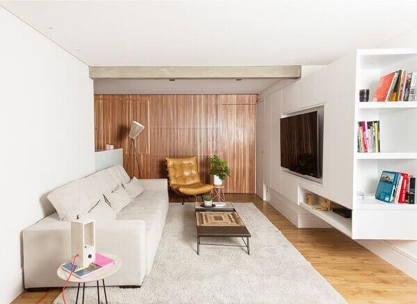 Poltrona capitonê caramelo próxima a parede