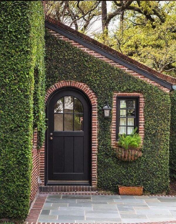 O acabamento da arandela colonial preta conversa com os tons da porta e janela