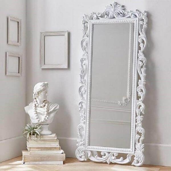 O espelho branco vintage de chão complementa a decoração clean
