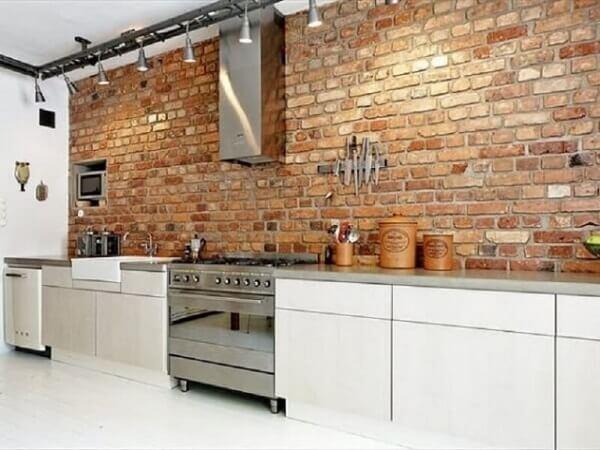 O revestimento de parede tijolinho se estende por toda a bancada da cozinha