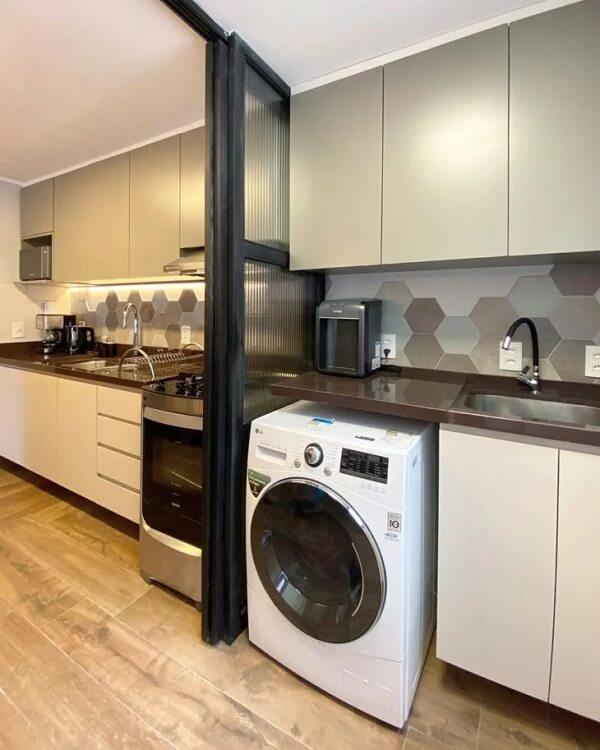 O revestimento hexagonal da lavanderia segue a mesma cor da cozinha