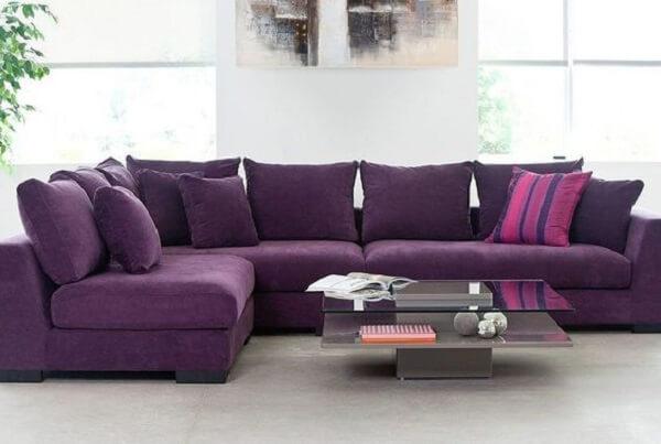 O sofá de canto roxo acomoda familiares e amigos no ambiente